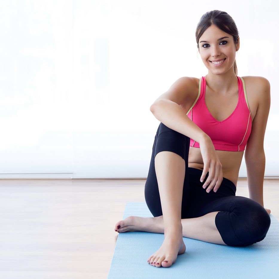 Portrait of beautiful healthy young woman doing exercise at home.